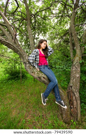 lovely girl in the deep forest sitting on branches