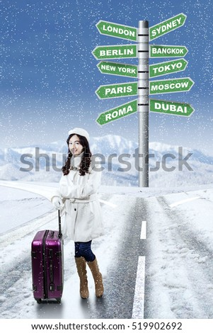 Lovely girl in winter clothes standing on the road with destination choices for winter holiday