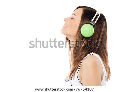 Lovely girl listening a music in headphones, white background - stock photo