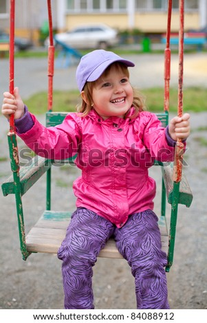 Lovely girl swinging at the schoolyard - stock photo