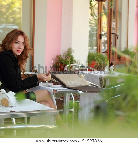 Lovely girl with a lovely smile relaxing in a cafe outdoors