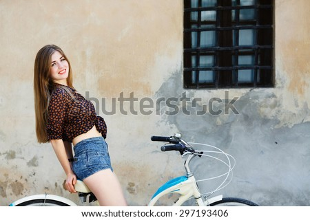 Lovely girl with long fair hair wearing on dark blouse and blue shorts is sitting on the bicycle on the old wall background - stock photo