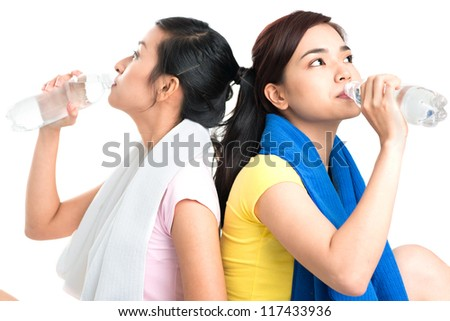 Lovely girls drinking water after intense workout - stock photo
