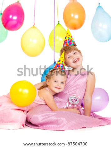 Lovely girls in party hats, embracing - stock photo