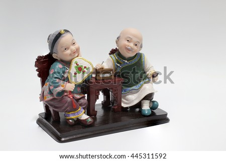 lovely grandparent doll siting rocking bamboo chair with playing checkerboard and playng card