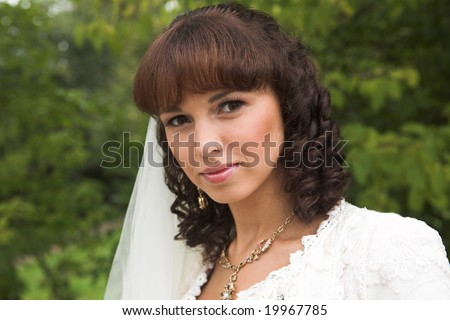 Lovely, happy bride walking in a park after marriage.