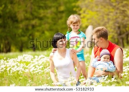 Lovely happy family enjoying time on the meadow