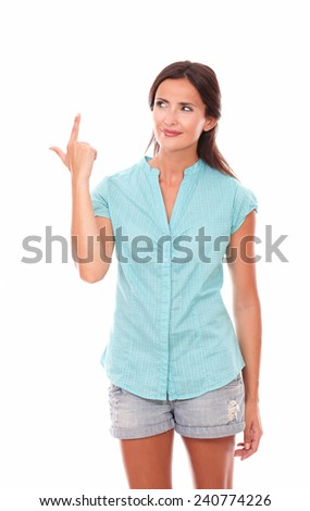 Lovely hispanic woman in blue blouse pointing up while looking to her right in white background - copyspace - stock photo