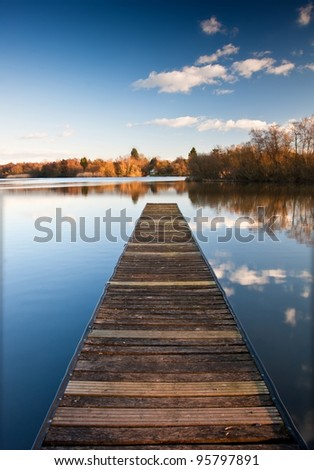 Lovely image of late sunset sky over calm lake landscape with long fishing jetty pier and vibrant colors - stock photo