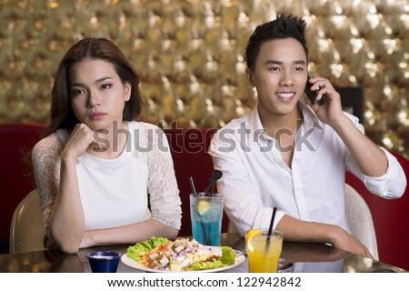 Lovely lady being annoyed with her boyfriend talking on the phone in the middle of the date - stock photo