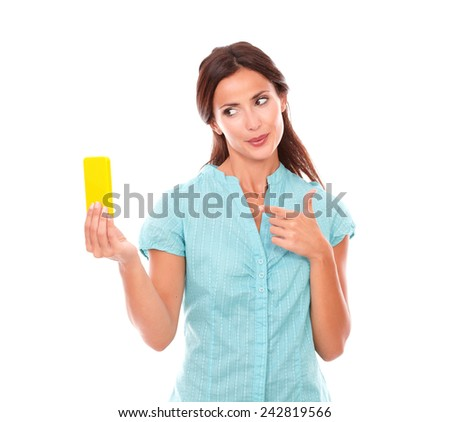 Lovely latin woman taking photos of herself or selfie using a yellow mobile phone while smiling in white background - stock photo