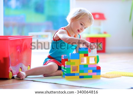 Lovely laughing little child, blonde girl of preschool age playing with colorful blocks sitting on a floor in a sunny room with a big window at home or kindergarten - stock photo