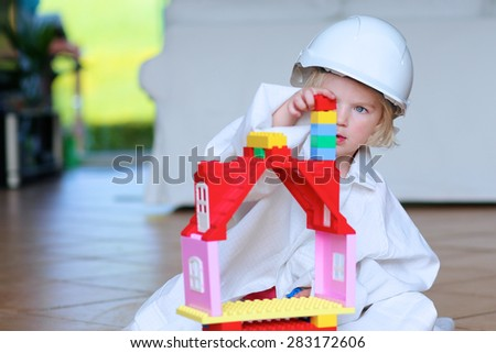 Lovely laughing little child, preschool age toddler girl wearing safety helmet playing indoors building house with colorful blocks sitting on a floor in big playroom at home or kindergarten - stock photo