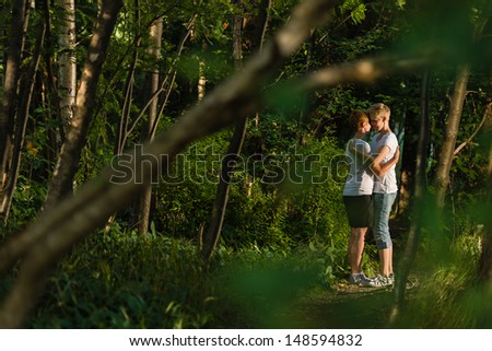 Lovely lesbian couple walks together in forest, evening