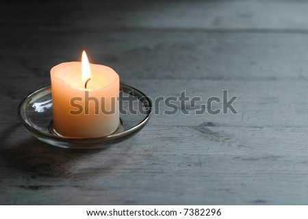 lovely lit candle on light wooden table - stock photo