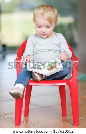 Lovely little baby girl sitting indoors on a small red plastic chair reading children book about animals - stock photo