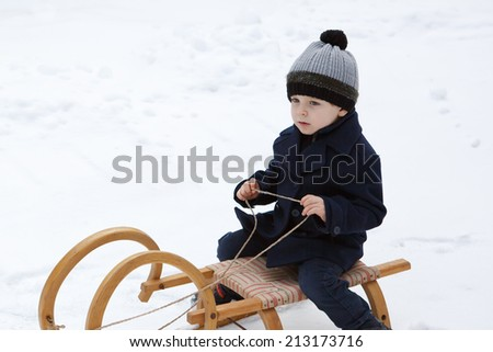 Lovely little boy having fun on ancient sledge on winter snow day - stock photo