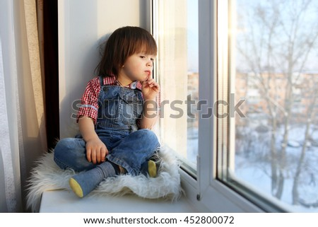 Lovely little boy sits on sill and looks out of window - stock photo