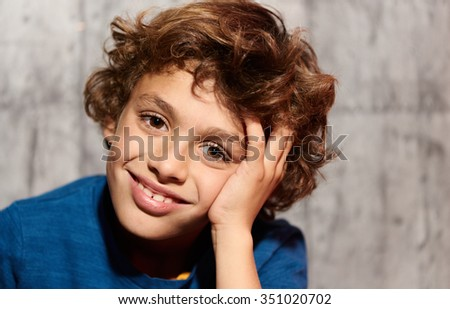 Lovely little boy with curly hair smiling at camera while sitting against of grey background - stock photo