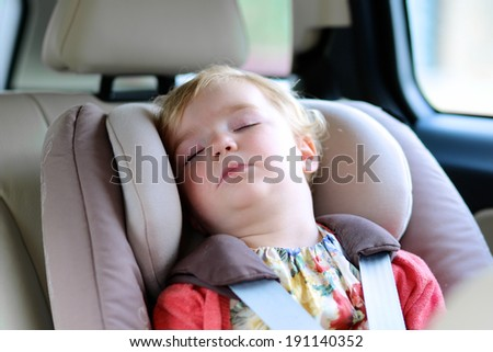 Lovely little child, cute blonde curly toddler girl peacefully sleeping in the car sitting in a baby seat with belt enjoying a family vacation trip in a modern safe vehicle - stock photo