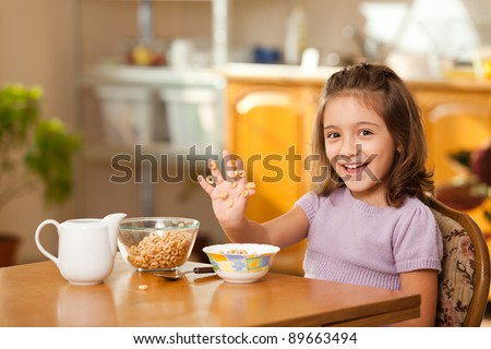 lovely little girl having breakfast: laughing at sticky cereals on her hand