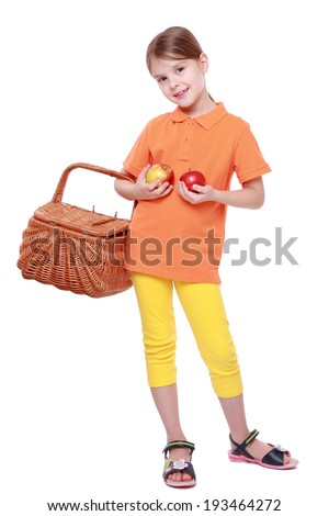 lovely little girl holding yummy apples and picnic basket isolated over white background