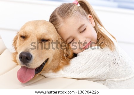 Lovely little girl hugging pet dog with passion, eyes closed. - stock photo