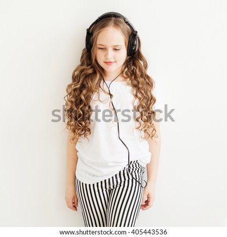 Lovely little girl in big headphones enjoy with a music - stock photo