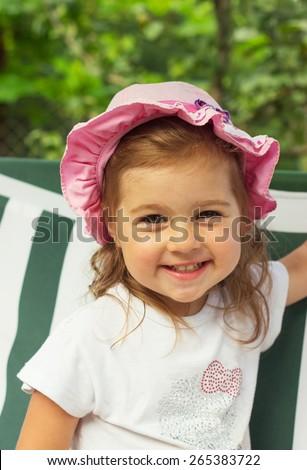 Lovely little girl is smiling outdoors - stock photo