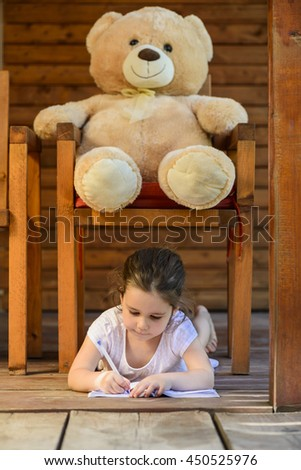 Lovely little girl lying down on the floor under a chair with teddy bear drawing on notebook outdoor on backyard terrace. Playing with teddy bear at home. Childhood happiness concept. - stock photo