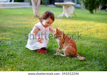 Lovely little girl playing with a cat on green garden - stock photo