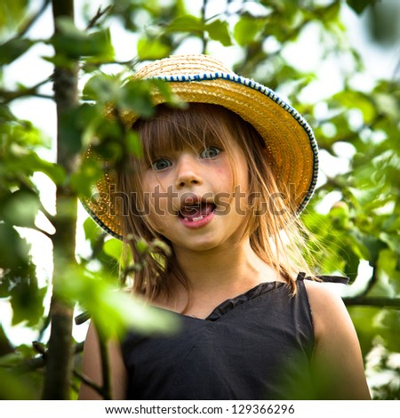 Lovely little girl posing in a straw hat in the park - stock photo