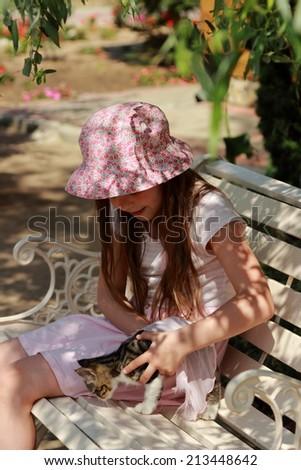 Lovely little girl sitting on the bench in park - stock photo