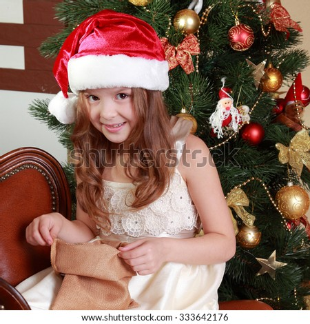 Lovely little girl with bag gift on Christmas on Holiday theme/Adorable little girl wearing gorgeous dress over Christmas decoration with Christmas gift - stock photo