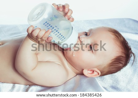 lovely little girl with blue eyes lying on her back in diapers and drinking milk from a bottle