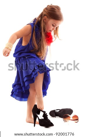 lovely little girl with evening make-up put on mother's heels isolated on white - stock photo