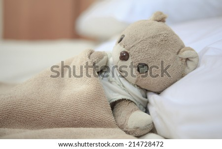 lovely little teddy bear.It is sleeping on the bed and pillow.