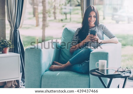 Lovely message from him. Beautiful young smiling woman looking at her smart phone while sitting in a big comfortable chair at home  - stock photo