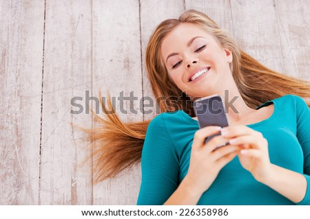 Lovely messages. Top view of beautiful young woman lying on the floor at her apartment holding phone - stock photo