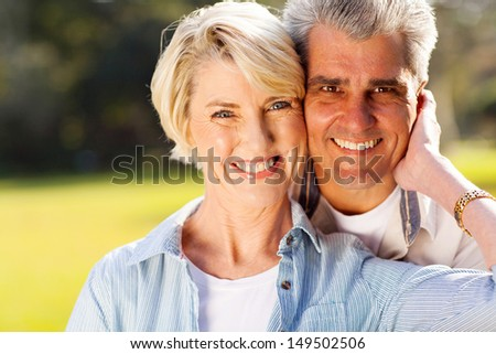 lovely mid age husband and wife portrait outdoors - stock photo