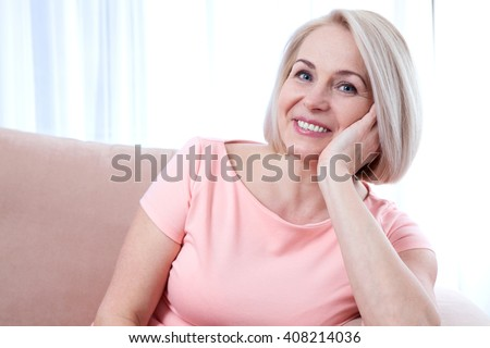 Lovely middle-aged blond woman with a beaming smile sitting on a sofa at home looking at the camera - stock photo
