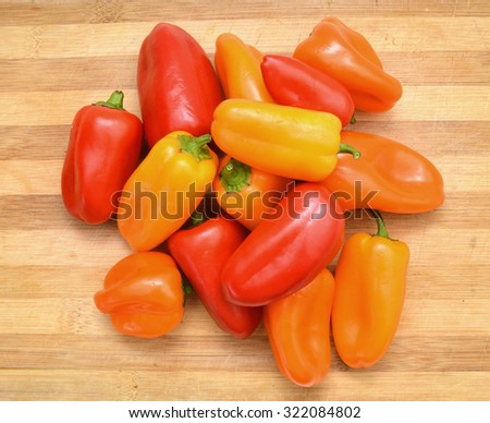 lovely mini peppers on wooden board - stock photo