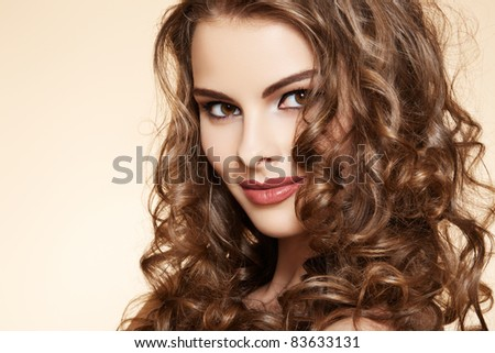 Lovely model with shiny  volume curly hair. Pin-up style on beige background - stock photo