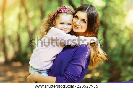 Lovely mother and child walking in the park - stock photo