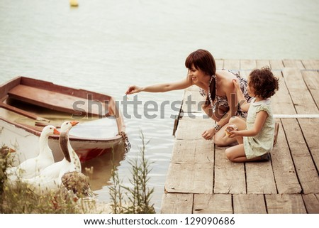 Lovely mother and daughter feeding gooses on the lake - stock photo