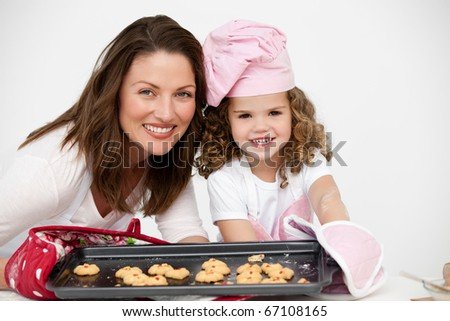 Lovely mother and daughter holding a plate with biscuits in the kitchen - stock photo