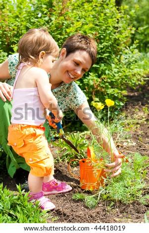 Lovely mother and toddler girl gardening - stock photo