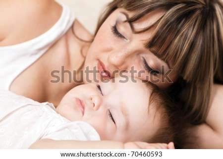 Lovely mother with her little daughter sleeping in bed. Focus on baby - stock photo