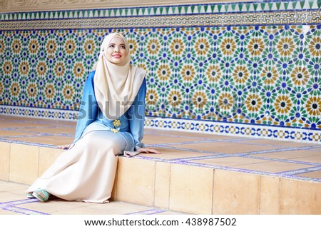 lovely muslim girl sitting in front of beautiful islamic pattern wall - stock photo