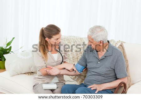 Lovely nurse helping her patient to do exercises at home - stock photo